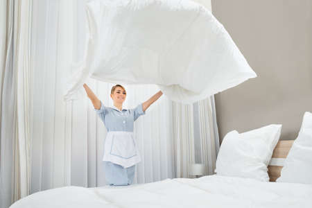 Happy Female Chambermaid Making Bed In Hotel Room