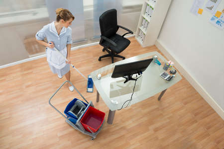 High Angle View Of Female Janitor Cleaning Floor With Mop In Office