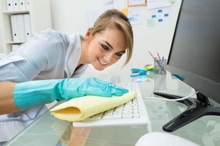 maid: Retrato de joven feliz de la criada de limpieza del teclado en el escritorio en la oficina