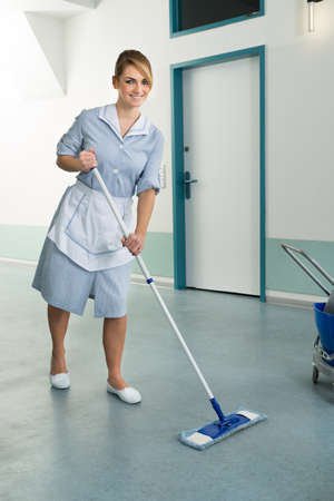 brooming: Young Happy Female Janitor Cleaning Floor Of Corridor Pass