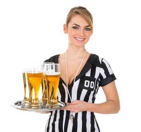 arbitros: Bandeja Holding joven Mujer Árbitro Con El Vidrio De Fondo Cerveza Sobre Blanco
