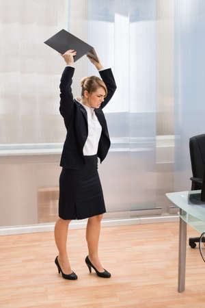 rage: Young Businesswoman In Rage Throwing Laptop At Workplace