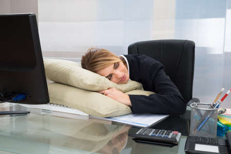 office sleeping pillow. Young Businesswoman Sleeping On Pillow At Desk In Office Photo O
