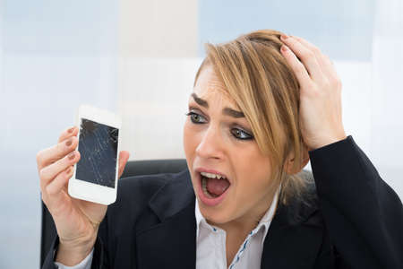 repair: Close-up Of Worried Businesswoman Holding Broken Screen Smartphone In Office Stock Photo