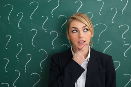 contemplated: Contemplated Businesswoman In Front Of Chalkboard With Question Mark Sign Stock Photo