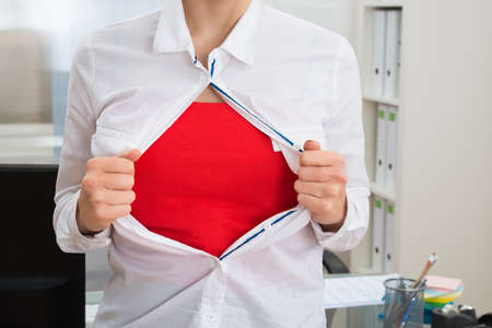 mystery woman: Close-up Of Businesswoman In Office Tearing Off Her Shirt Showing Red Costume Stock Photo