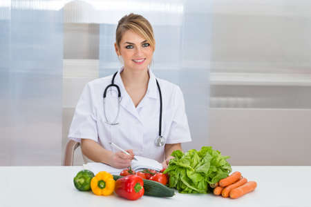 dietician: Portrait Of Happy Female Dietician With Fresh Vegetables And Diary
