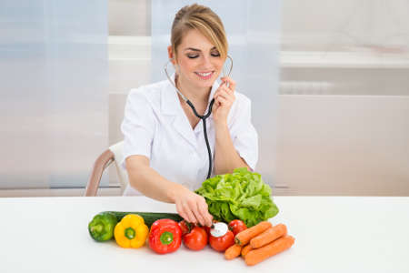 dietician: Happy Female Dietician Examining Fresh Vegetables With Stethoscope