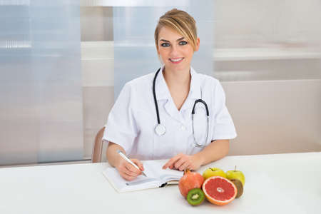 dietician: Female Dietician Writing Prescription With Fruits On Desk Stock Photo
