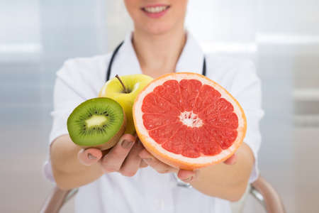 dietician: Close-up Of Happy Female Dietician Holding Fresh Sliced Fruits