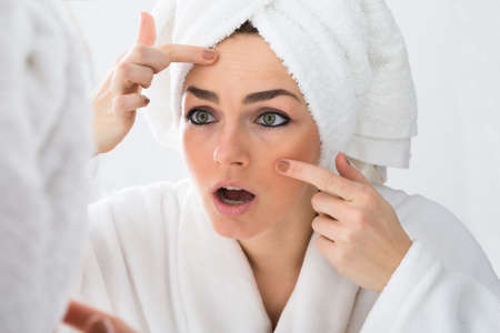 mirror face: Close-up Of Worried Woman Looking At Pimple On Face In Mirror Stock Photo