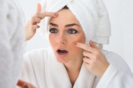 piel: Primer De La Mujer preocupante Mirando a la espinilla En Cara En Espejo Foto de archivo
