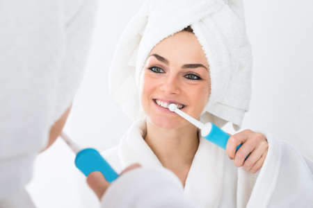 teeth cleaning: Close-up Of A Woman In Bathrobe Brushing Teeth