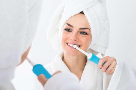 diente: Primer De Una Mujer En Albornoz cepillarse los dientes