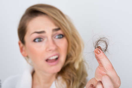 emotional woman: Close-up Of Worried Woman Holding Loss Hair Stock Photo