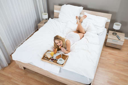 High Angle View Of A Woman Lying On Bed Having Breakfast photo