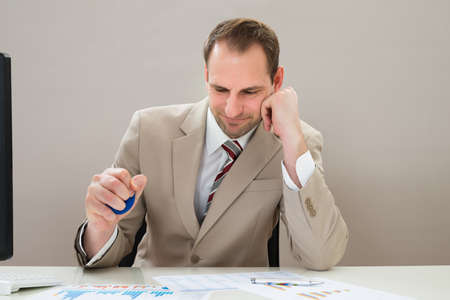 stress relief: Businessman Squeezing Blue Stress Ball At Desk