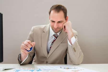 stress ball: Businessman Squeezing Blue Stress Ball At Desk
