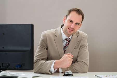 service desk: Businessman Using Service Bell At Desk In Office