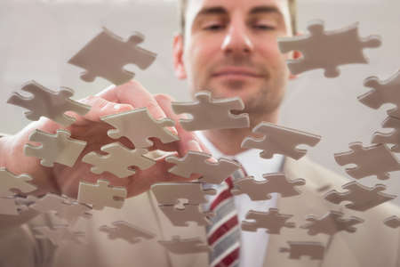 one piece: Businessman Separating Jigsaw Puzzle On Glass Table