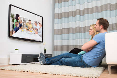 Couple Sitting On Carpet Watching Television In Living Room