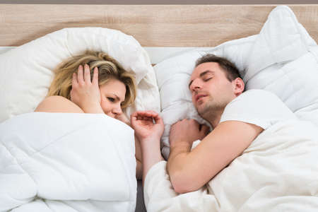 snoring: Woman Covering Ears While Man Snoring In Bed At Home