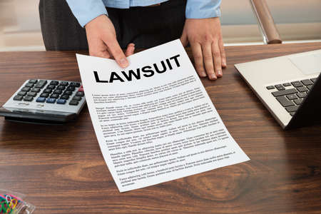 the litigation: Close-up Lawyer Showing The Document With The Text Lawsuit Stock Photo