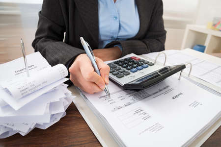 INVOICE: Close-up Of Businessperson Calculating Bills At Desk