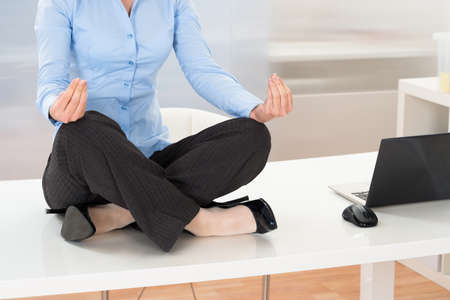 Close-up Of Businesswoman Doing Yoga In Office Stock Photo