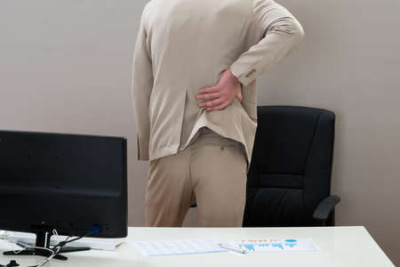 Close-up Of Businessman Suffering From Backache In Office photo