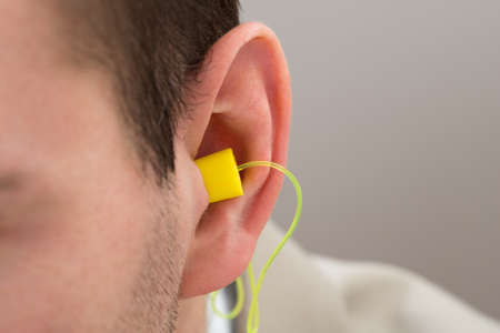 stop pollution: Close-up Of Yellow Earplug Into The Ear Of Person