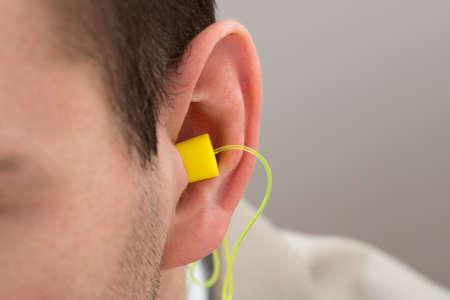 protección: Primer De auricular amarillo en el oído de la persona