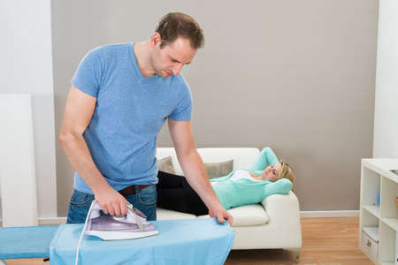 the iron lady: Man Ironing Clothes While Woman Relaxing On Sofa At Home Stock Photo
