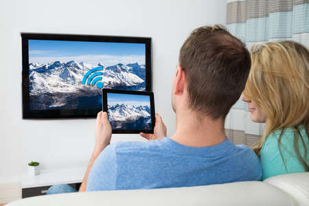 digital television: Couple Connecting Television Channel Through Wifi On Digital Tablet