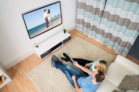 television: Couple Changing Channel With Remote Control In Front Television Stock Photo