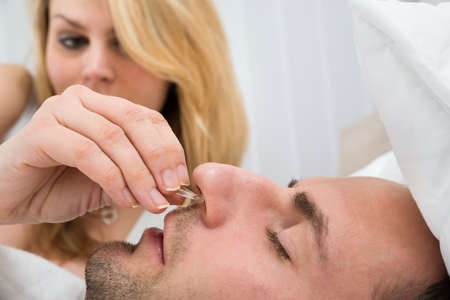 snoring: Close-up Of Woman Inserting Nose Clip Device Into Sleeping Man Nose Stock Photo