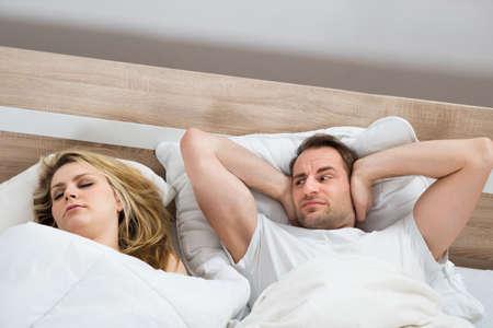 여자가 집에서 침실에서 잠자는 동안 귀를 덮고있는 남자