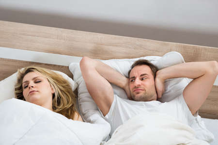 Man Covering Ears While Woman Sleeping In Bedroom At Home
