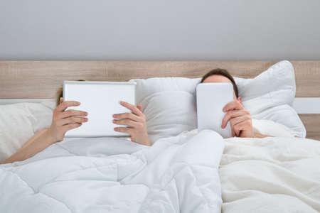 couple bed: Couple au lit avec tablettes num�riques En Chambre