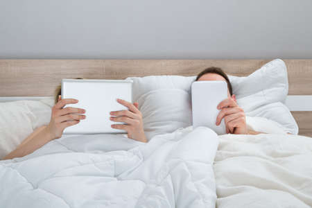 mid adult couple: Couple Lying In Bed With Digital Tablets In Bedroom