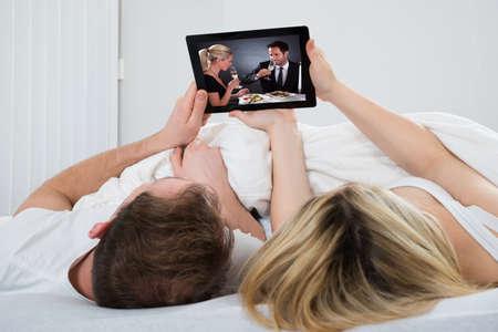 Paar dat in bed Kijken Video On Digital Tablet Stockfoto