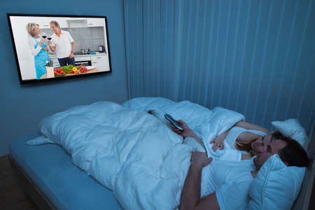 Couple Lying In Bed With Blanket Watching Television Stock Photo