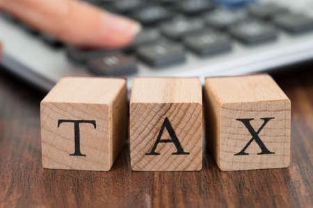 ingresos: Primer De La Persona Mano usando la calculadora con el impuesto palabra en bloques de madera