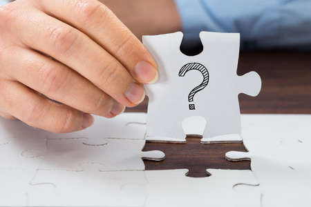 jigsaw puzzle pieces: Close-up Of Person Hand Holding Puzzle With Question Mark Sign