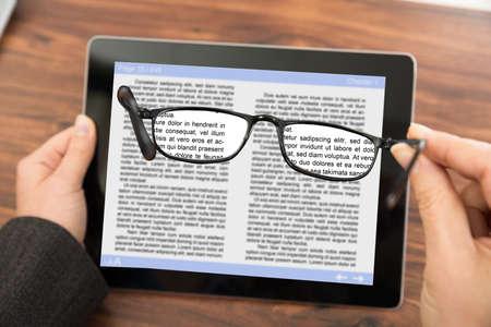 persona leyendo: Primer De La Persona Lectura de libros electr�nicos en la tableta digital con Gafas