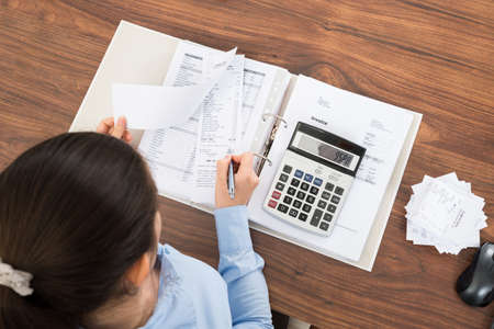 tax: Businesswoman Calculating Tax At Desk With Calculator In Office