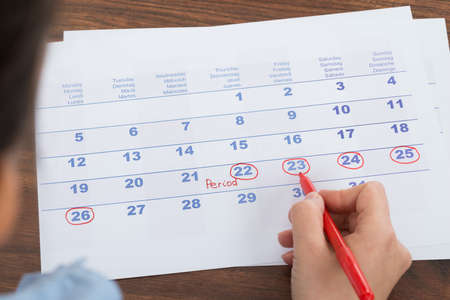 menses: Close-up Of Person Marking Menses Date On Calendar Stock Photo