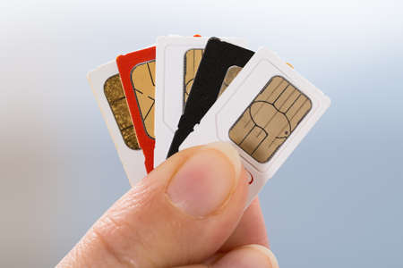 Close-up Of Person Hand Holding Four Phone Sim Cards Stock Photo