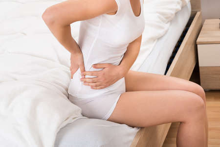 Close-up Of Female Sitting On Bed Having Backache photo