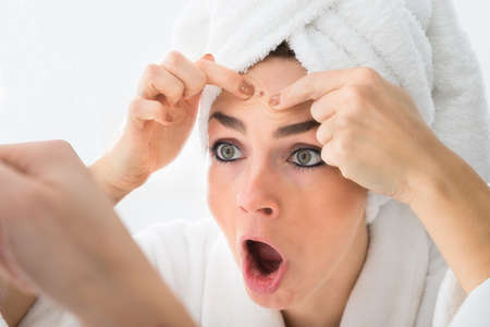 Shocked Woman Looking At Pimple On Forehead In Mirror Stock Photo